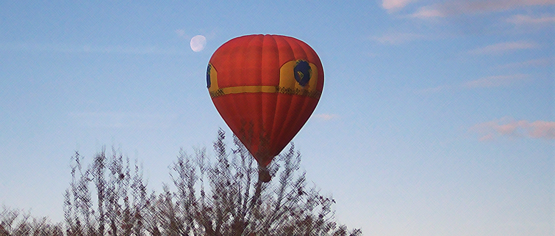 Red air balloon against early morning sky with moon behind it