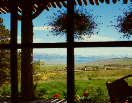 A view from a lovely cabin of the open prairie and mountains in the distance.
