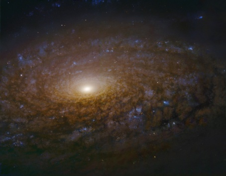 A whirlpool of stars in outerspace, with a bright planet or star in the center.